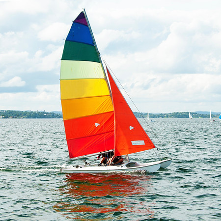 Children Sailing small sailboat boat with a Colourful Sails on an inland waterway.