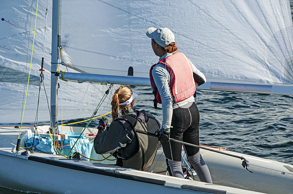 Two girls one standing other sitting sailing a racing skiff closeup.