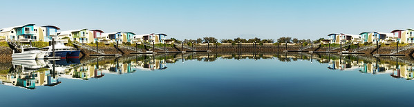 Super panoramic waterfront marina/dock/resort with boats and clear water reflections.