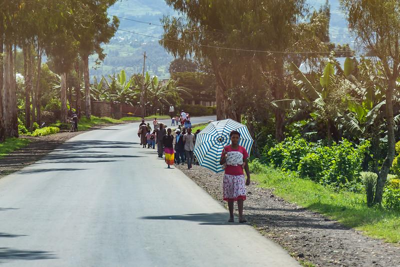 woman with  umbrella along the road - Uganda-7527