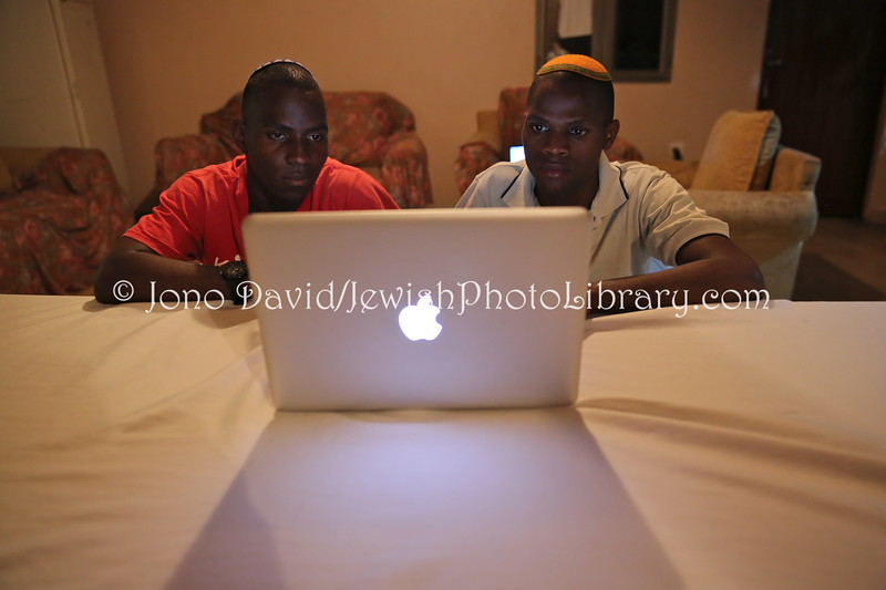 UG 328  Rabin Asiimwe (L) and Samson Nderitu looking at photos, Guest House