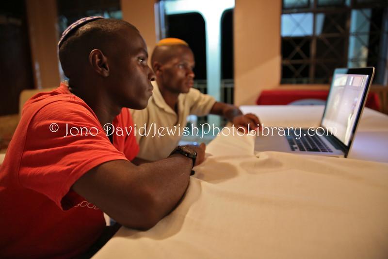 UG 327  Rabin Asiimwe (L) and Samson Nderitu looking at photos, Guest House