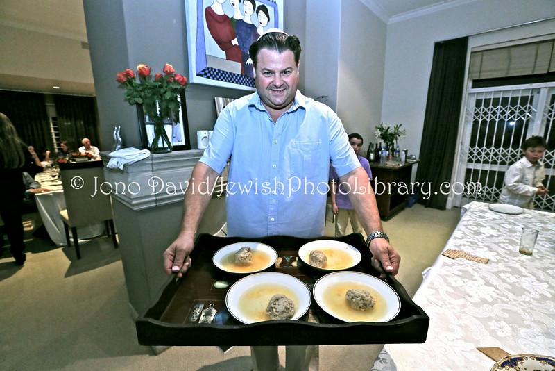 ZA 14297  Host Dov Werb serves matzoh ball soup