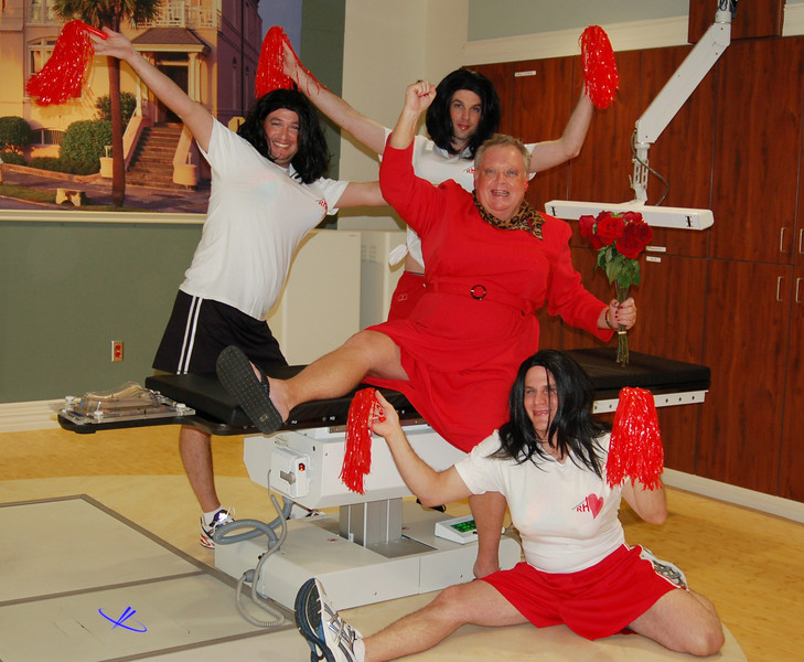 """The Red Dress is the national symbol of Heart Disease awareness. On 9/12 the gentleman in whose name we raise the most money for AHA will wear the Red Dress to the hospital cafeteria. Richard and his cheerleaders, Adam, Shawn and Jason represent the """"Rah, Rah, Radiation"""" Radiation Oncology Team. Click <a href=""""http://heartwalk.kintera.org/lowcountrysc/richard"""">here</a> to donate online to Richard."""