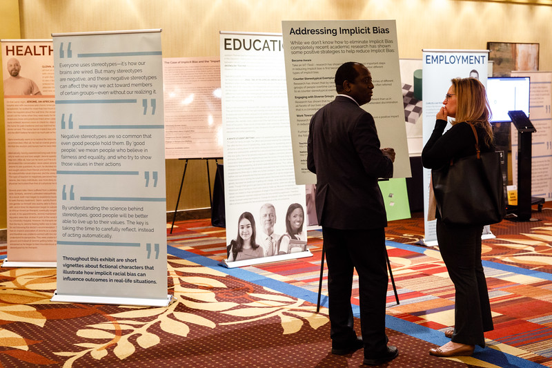 Attendees look at the diversity booth display during day