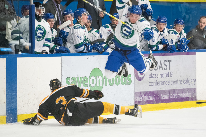 Noah Williams (10) goes airborne over Olds Grizzlies defencman Austin Pickford (3) during the home opener of the AJHL 2017 Regular Season between the Calgary Canucks and the Olds Grizzlies 9 17 at the Max Bell Centre.