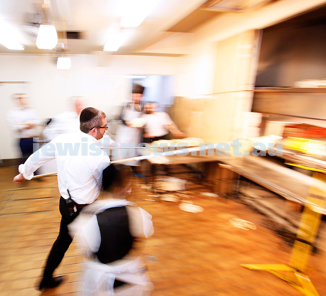 Manic matzah mayhem. It's 18 minutes of oraganised chaos over and over again at the Adass Israel Synagogue with all hands on deck to mix, knead, roll and finally bake traditional shmurah matzahs in a wood fired oven in time for the seders. Photo: Peter Haskin