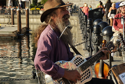 Dave Harris, the one man band and busker of Victoria, plays his hillbilly train song on the harbor sidewalk.