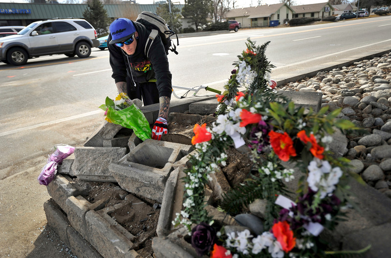 Levi Ledford, of Longmont, places flowers at a temporary memorial, Thursday, March 7, 2013, at the corner of 17th Ave. and Main Street in Longmont.<br /> (Matthew Jonas/Times-Call)