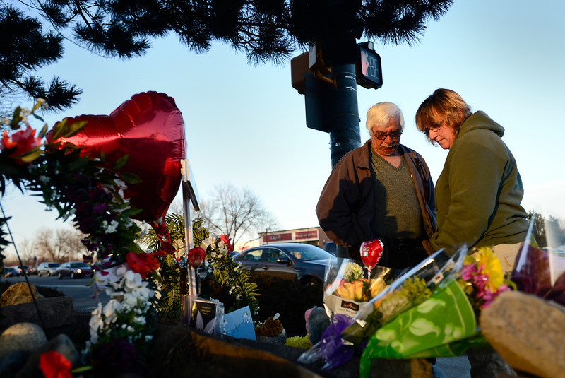 Gus Schiavon and Myrna Schiavon pause a moment to view a temporary memorial, Thursday, March 7, 2013, at the corner of 17th Ave. and Main Street in Longmont. The Schiavon's left a card at the scene.<br /> (Matthew Jonas/Times-Call)