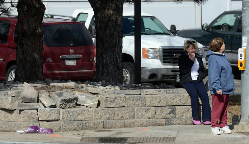 After placing flowers on the sidewalk, a woman, left, sits on a retaining wall during an investigation Thursday morning March 7, 2013 after Wednesday night's fatal accident at 17th Avenue and Main Street.  (Lewis Geyer/Times-Call)