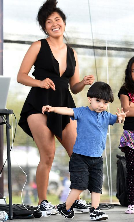 . Zol Trujillo, 3, shows off his dance moves with Lolita Mendoza on Saturday. Longmont held its annual Cinco de Mayo celebration at Roosevelt Park on Saturday. For more photos and a video, go to dailycamera.com. Cliff Grassmick  Photographer  May 5,  2018