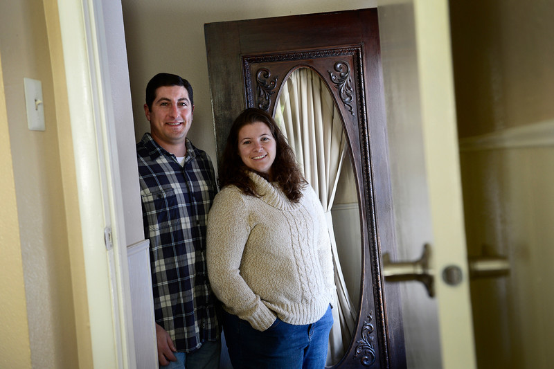 Dave Gaccetta and Becky Gaccetta pose for a portrait, Wednesday, Dec. 19, 2012, next to a door that belonged to Dave Gaccetta's his great grandparents' home built in 1912 in Denver. The door now resides at their home in Longmont.<br /> (Matthew Jonas/Times-Call)