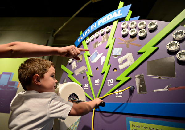 """20121119_AMPD_061.jpg Andrew Telgenhof, 9, points as his brother Adam, 5, powers a hand crank while exploring the AMP'D exhibit at the Longmont Museum & Cultural Center on Monday, Nov. 19, 2012.  The exhibit, which is open through February 17, features many hands-on activities and information about the centennial of Longmont Power & Communications.  For more photos and a video visit  <a href=""""http://www.TimesCall.com"""">http://www.TimesCall.com</a>.<br /> (Greg Lindstrom/Times-Call)"""