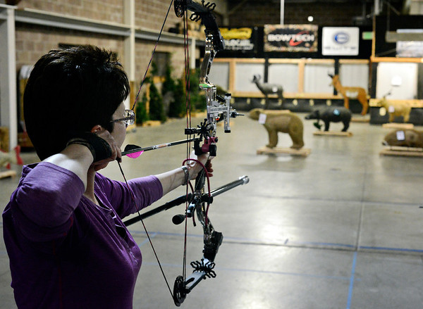 Michele Dawe takes aim during a 3-D shoot at Archery in the Wild in Longmont on Wednesday, Jan. 30, 2013. <br /> (Greg Lindstrom/Times-Call)