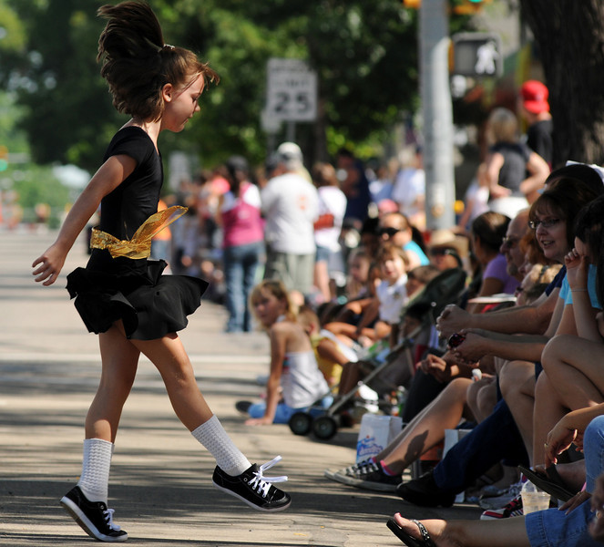 A young performer with the Martin Percival School of Irish Dance performs for the crowd along Main Street in Longmont during the Boulder County Fair Parade, July 31, 2010.