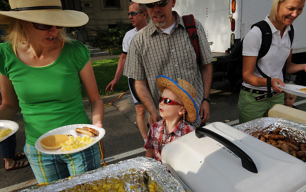 Jennifer Knievel, left, her four-year-old son Eli Knievel and husband Jason pick up their meals during the Twin Peaks Rotary Chuck Wagon Breakfast in Longmont Saturday, July 31, 2010. (Bradley Wakoff/Times-Call)