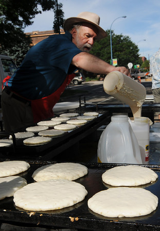 Volunteer Mike Pipis pours pancake batter during the Twin Peaks Rotary Chuck Wagon Breakfast in Longmont Saturday, July 31, 2010. (Bradley Wakoff/Times-Call)