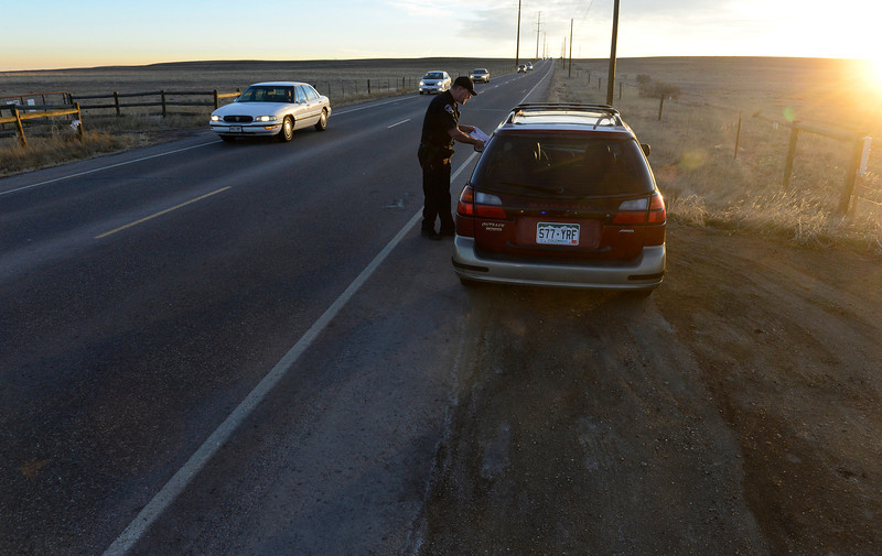 Boulder County Sheriff's deputy Keith Powell gives a ticket to a motorist he pulled over on Lookout Road, near North 79th Street, Friday morning, Jan. 25, 2013. (Lewis Geyer/Times-Call)