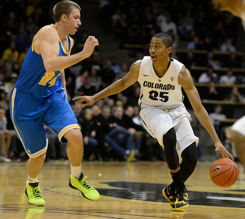 The University of Colorado's Spencer Dinwiddie looks for an open man in front of UCLA's Travis Wear in the first half Saturday Jan. 12, 2013 at the Coors Events Center. (Lewis Geyer/Times-Call)