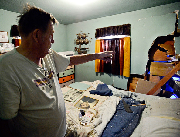 "Ken Barkman points to a hole in the wall of his bedroom after a car ran into his house at 914 Collyer St. in Longmont on Monday, Dec. 24, 2012. Barkman was in the opposite corner of the room when the crash occurred. For more photos and a video visit  <a href=""http://www.TimesCall.com"">http://www.TimesCall.com</a>.<br /> (Greg Lindstrom/Times-Call)"