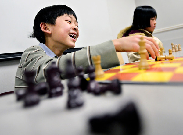 "Alex Fong, 7, laughs while playing against his brother, Andrew Fong, during chess club at the Longmont Public Library on Monday, Feb. 4, 2013. For more photos and a video, visit  <a href=""http://www.TimesCall.com"">http://www.TimesCall.com</a>.<br /> (Greg Lindstrom/Times-Call)"