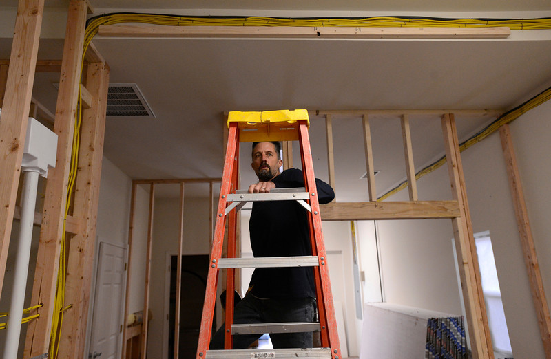 Dustan Flanagan climbs a ladder to start framing around wiring, Saturday, Nov. 24, 2012, at Carbon Valley Coffee Roasters in Frederick.<br /> (Matthew Jonas/Times-Call)