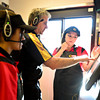 Corporate trainer Dennis Pollock, center, teaches Miranda Carrillo, left, and Vanessa Chavez how to take orders and operate monitors during a training session at Taco John's in Longmont on Monday, Jan. 21, 2013. <br /> (Greg Lindstrom/Times-Call)