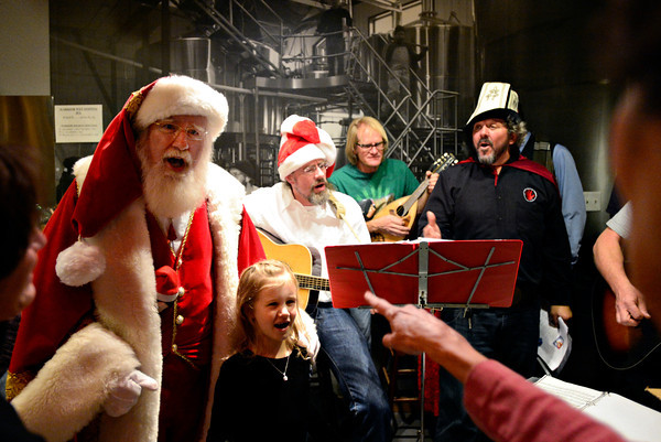 """Janet Pearson points to her granddaughter, Lauren Casey, 6, while singing """"Feliz Navidad"""" with Santa Claus and the """"Boys from the Brew House"""" during the """"Our Gift to the OUR Center"""" toy drive at Left Hand Brewing Co. on Friday, Dec. 21, 2012. Casey and her family brought more than 100 toys to the event, many of which came from a celebration for Janet's husband, Bernard """"Buzz"""" Pearson, which took place earlier in the day. Buzz passed away on Dec. 4, 2012, after 48 years of marriage to Janet. He was 68. The toys donated at Left Hand Brewing Co. will be delivered to the OUR Center on Christmas morning.<br /> (Greg Lindstrom/Times-Call)"""
