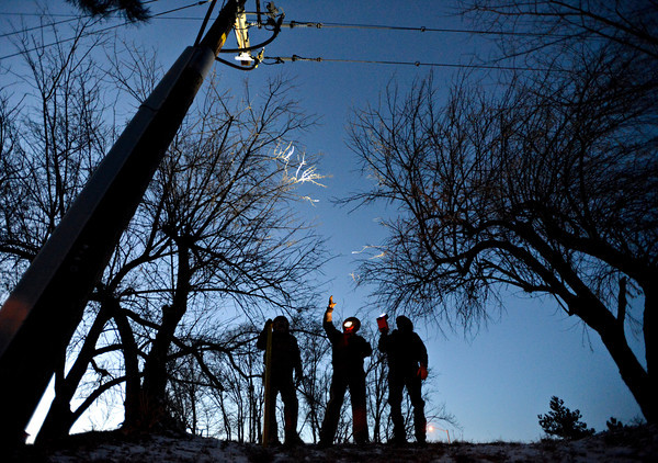 Longmont Power & Communications employees, left to right, Clay Sharp, Kenny Beecher and Mike Zavala inspect power lines just south of the intersection of South Hover Road and Ken Pratt Boulevard on Monday, Jan. 14, 2013. Callers reported a sparking wire near the intersection just before 5 p.m., but Longmont Power & Communications employees attributed the outage to a blown transformer. The power outage caused traffic signals to briefly go out at the intersections of South Hover Road and Pike Road, as well as Sunset Street and Ken Pratt Boulevard.<br /> (Greg Lindstrom/Times-Call)