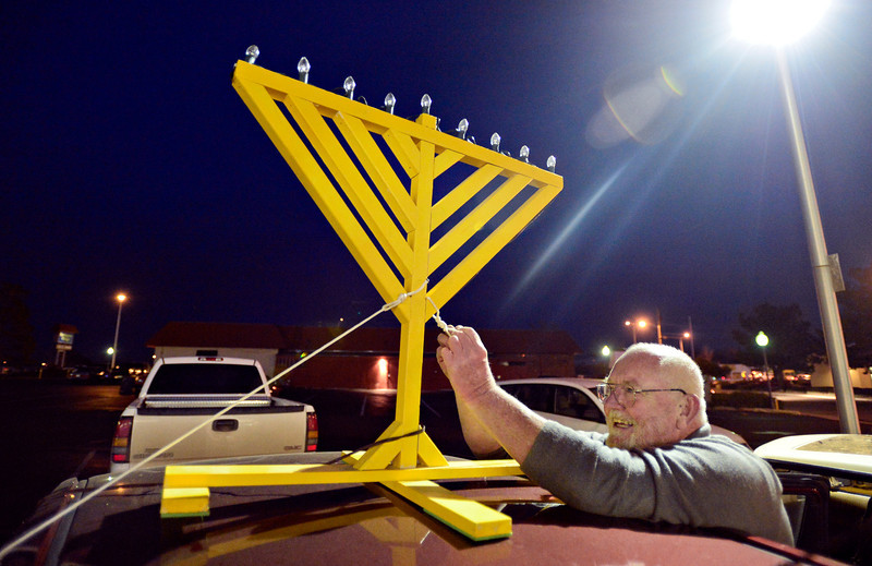 "Larry Box, of Longmont, attaches a wooden menorah to the top of his car at the Chabad Jewish Center of Longmont before a Hanukkah parade through Longmont on Thursday, Dec. 13, 2012. About 20 cars participated in the parade during its second year. For a video visit  <a href=""http://www.TimesCall.com"">http://www.TimesCall.com</a>.<br /> (Greg Lindstrom/Times-Call)"