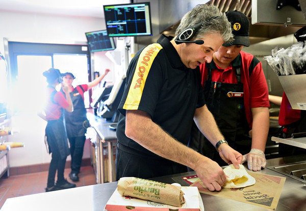 Corporate trainer Dennis Pollock, center, teaches Dustin Vialpando, right, proper folding techniques during a training session at Taco John's in Longmont on Monday, Jan. 21, 2013. <br /> (Greg Lindstrom/Times-Call)