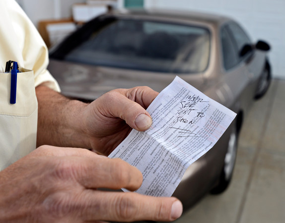 """Paul Ferruzza, 63, is the first motorist in Longmont to be ticketed in suspicion of texting while operating a motor vehicle.  He plans to fight the ticket in court. Ferruzza shows his citation at his home in Longmont on Wednesday, Dec. 5, 2012. For a video visit  <a href=""""http://www.TimesCall.com"""">http://www.TimesCall.com</a>.<br /> (Greg Lindstrom/Times-Call)"""