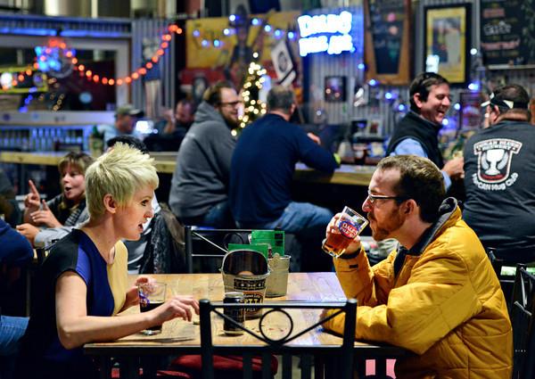 Caitlin Gibbons, left, of Denver, and Nate Wessel, of Longmont, enjoy a beer at Oskar Blues Tasty Weasel Tap Room in Longmont on Monday, Dec. 17, 2012.<br /> (Greg Lindstrom/Times-Call)