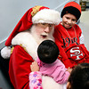 Santa Claus makes a face at Maria Garcia while she and her siblings, Juan, 9, right, and Mayte, 3, wait to receive gifts at the OUR Center in Longmont on Tuesday, Dec. 25, 2012. <br /> (Greg Lindstrom/Times-Call)