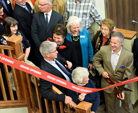 Guests lean away as Mayor Dennis Coombs, right, prepares to cut a ribbon during the dedication ceremony for The Hearthstone at Hover Crossing in Longmont on Tuesday, Jan. 15, 2013.<br /> (Greg Lindstrom/Times-Call)