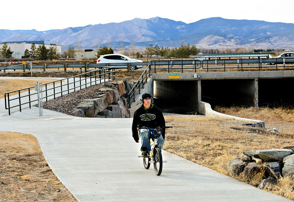 Tyler Martinez, 19, rides along the St. Vrain Greenway near Airport Road on Monday, Dec. 10, 2012. The trail ends just west of Airport Road.<br /> (Greg Lindstrom/Times-Call)