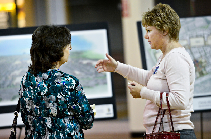 "Shirley McNeff, left, and Christina Clark discuss artist renderings during the Longmont Area Chamber of Commerce Business After Hours, hosted by NewMark Merrill Mountain States, at Twin Peaks Mall on Thursday, Jan. 17, 2013. Kathy Weber-Harding, president and CEO of the Longmont Area Chamber of Commerce, said she expected a large turnout for the first Business After Hours of the year, given the interest surrounding the redevelopment of Twin Peaks Mall. ""I would definitely attribute it to the mall and what is going to happen and what they're going to be doing,"" she said. ""I think people in this community want a mall that they can shop at and not have those retail dollars leaving this community."" Two hundred thirty people R.S.V.P'd for the event.<br /> (Greg Lindstrom/Times-Call)"