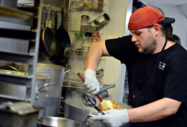 Travis McClinton prepares food at Georgia boys BBQ in Longmont on Friday, Feb. 8, 2013. <br /> (Greg Lindstrom/Times-Call)