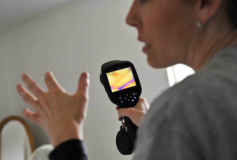 Nikki Chandler, of Ultimate Properties and Development, talks to home owner Matthew Kenworthy (not pictured) as she uses an infrared camera during an energy audit, Tuesday, Jan. 15, 2013, in Longmont.<br /> (Matthew Jonas/Times-Call)