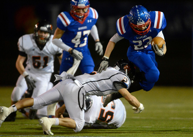 Erie High School's Pedro Anderson (No. 2) tries to tackle Centaurus High School's Tanner Martinelli (No. 23) during the third quarter, Friday, Nov. 2, 2012, at CHS. The Tigers defeated the Warriors, 37-20.<br /> (Matthew Jonas/Times-Call)