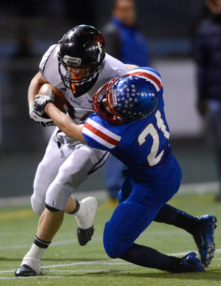 Erie High School's B.J. Jensen (No.34) tries to break a tackle from Centaurus High School's Shayne Alberston (No. 21) during the first quarter, Friday, Nov. 2, 2012, at CHS.<br /> (Matthew Jonas/Times-Call)