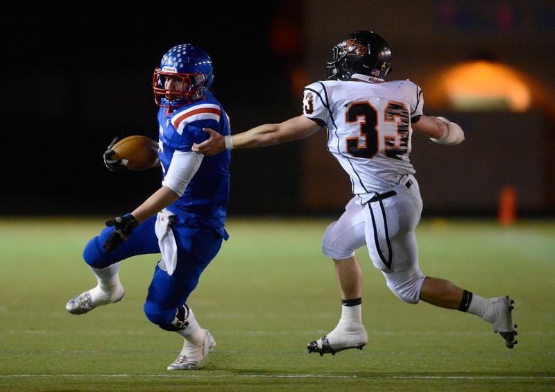 Centaurus High School's J.J. Scott (No. 5) tries to slide past Erie High School's Ryan Romey (No. 33) during the second quarter, Friday, Nov. 2, 2012, at CHS.<br /> (Matthew Jonas/Times-Call)