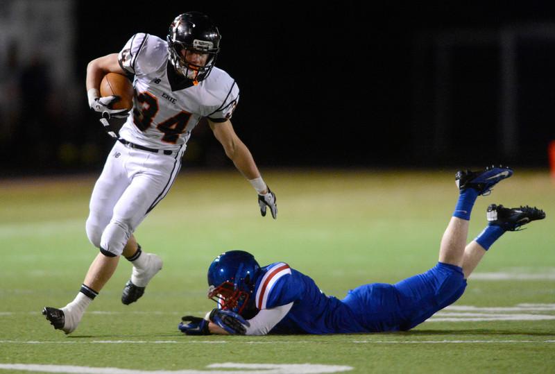Erie High School's B.J. Jensen (No. 34) moves past Centaurus High School's William Rowsam (No. 14) during the first quarter, Friday, Nov. 2, 2012, at CHS.<br /> (Matthew Jonas/Times-Call)