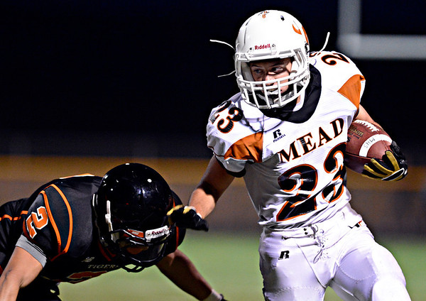 """Mead's Logan Anderson (23) tries to break away from Erie's Pedro Anderson (2) in the first half.  Erie beat Mead 24-0 on Friday, Sept. 21, 2012.  For more photos visit  <a href=""""http://www.BoCoPreps.com"""">http://www.BoCoPreps.com</a>.<br /> (Greg Lindstrom/Times-Call)"""
