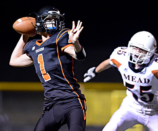 "Erie's Tristen Lyle (1) throws as he is pursued by Mead's Brandon Binkley (55) in the second half.  Erie beat Mead 24-0 on Friday, Sept. 21, 2012.  For more photos visit  <a href=""http://www.BoCoPreps.com"">http://www.BoCoPreps.com</a>.<br /> (Greg Lindstrom/Times-Call)"
