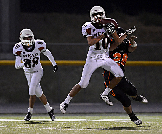 "Mead's Aaron Cheung (10) pulls in a pass over Erie's Joey Ramey (28) in the fourth quarter. Erie beat Mead 24-0 on Friday, Sept. 21, 2012.  For more photos visit  <a href=""http://www.BoCoPreps.com"">http://www.BoCoPreps.com</a>.<br /> (Greg Lindstrom/Times-Call)"