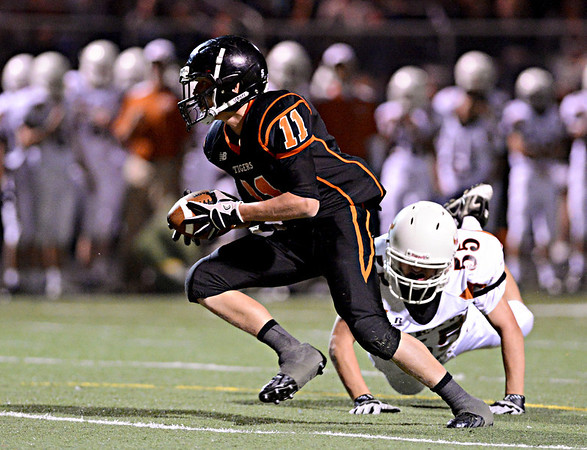 "Erie's B.J. Jensen (11) runs past Mead's Brandon Binkley (55) in the first half. Erie beat Mead 24-0 on Friday, Sept. 21, 2012.  For more photos visit  <a href=""http://www.BoCoPreps.com"">http://www.BoCoPreps.com</a>.<br /> (Greg Lindstrom/Times-Call)"