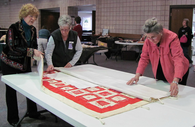 Members of the archives committee at First Evangelical Lutheran Church fold up a friendship quilt from 1895.
