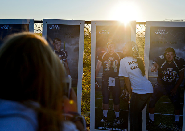 "Katelynn Campbell pretends to kiss a poster of her friend Ryan Miller, while fellow senior Courtney Zimmerman take a picture before the game.  Frederick beat Berthoud 41-14 during the game at Frederick High School on Friday, Sept. 14, 2012.  For more photos visit  <a href=""http://www.TimesCall.com"">http://www.TimesCall.com</a>.<br /> (Greg Lindstrom/Times-Call)"